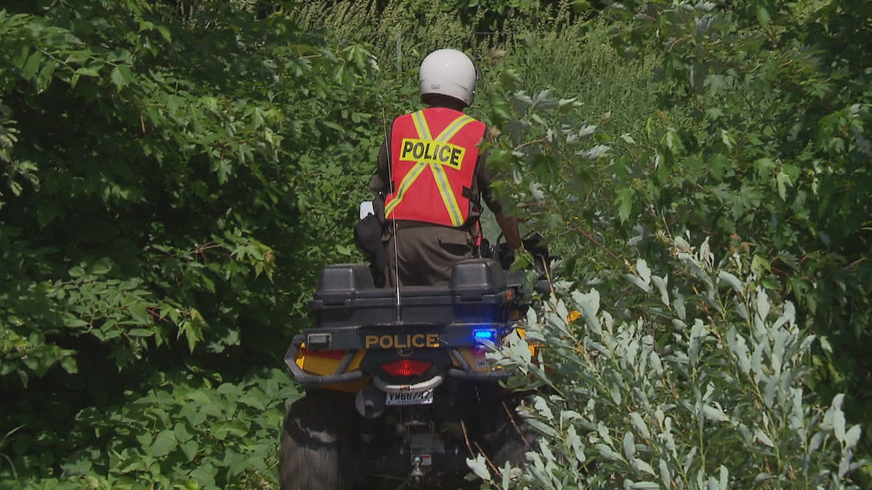 Policier sur un VTT dans un boisé