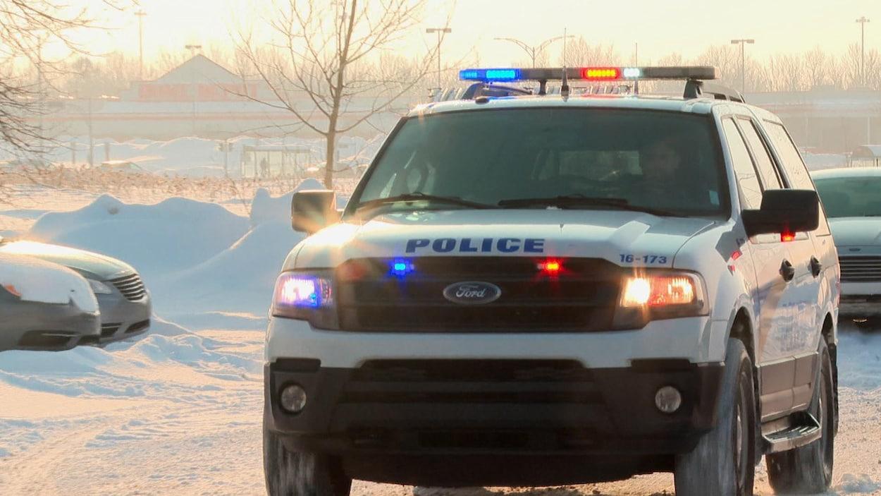 Un VUS de la police de Lévis, dont les gyrophares sont allumés, circule dans un stationnement, en hiver.