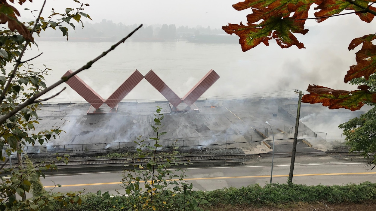 La statue en forme de W entourée de fumée.