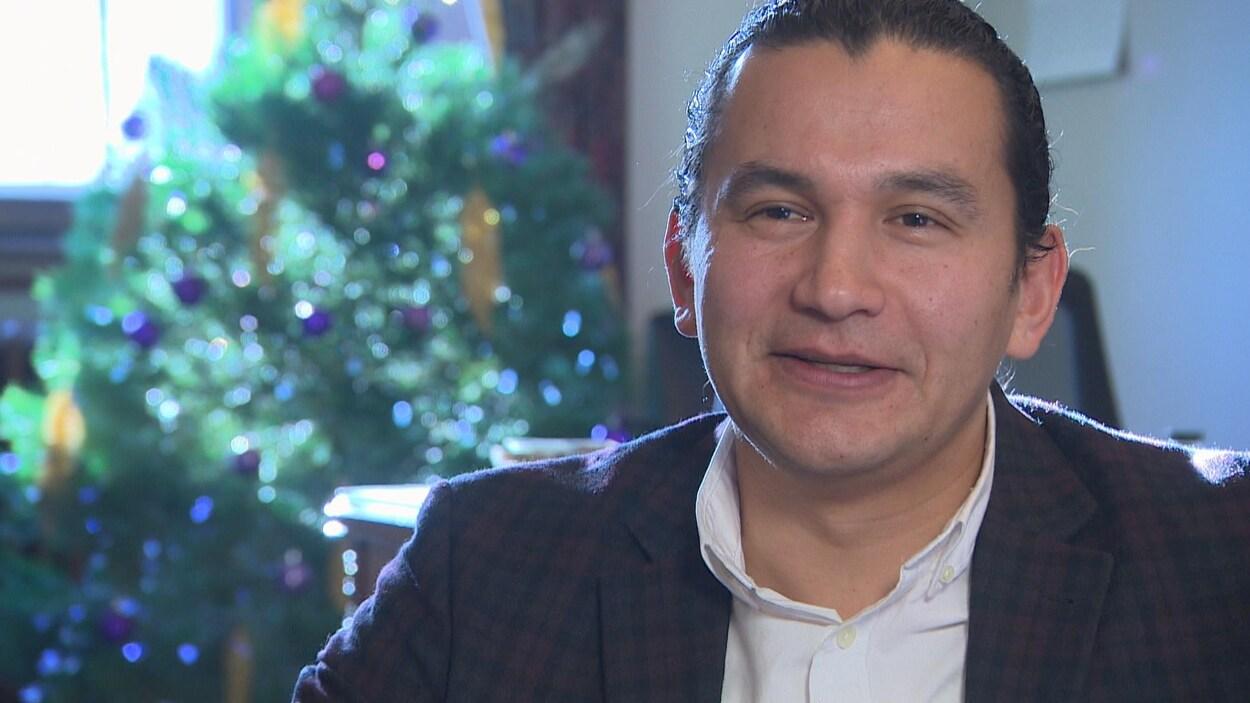 Gros Plan sur Wab Kinew, en entrevue avec Radio-Canada. Au fond derrière lui, on aperçoit un arbre de Noël et le coin de son bureau.