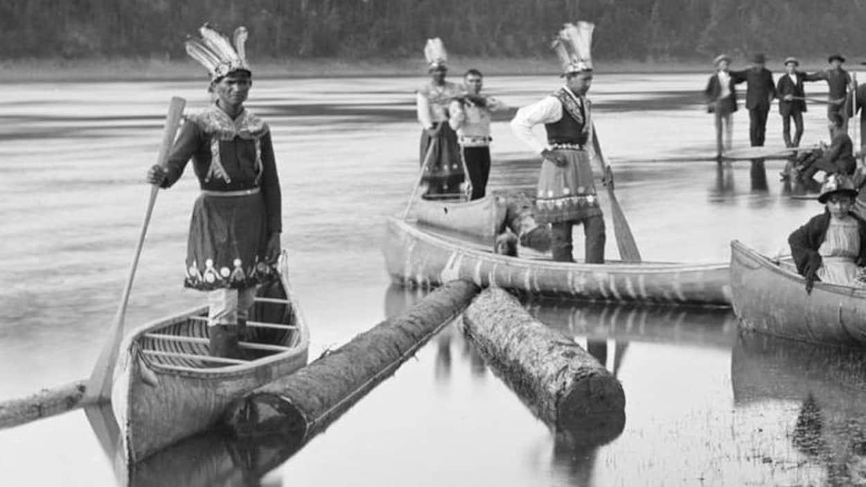 Les Malécites debout dans leurs embarcations sur les rives du village de Kingsclear, au Nouveau-Brunswick, célébrant la fête du Corpus Christi, vers 1887.