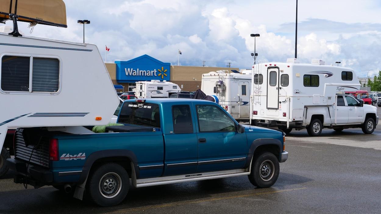 Des caravanes dans un stationnement devant le magasin Walmart.