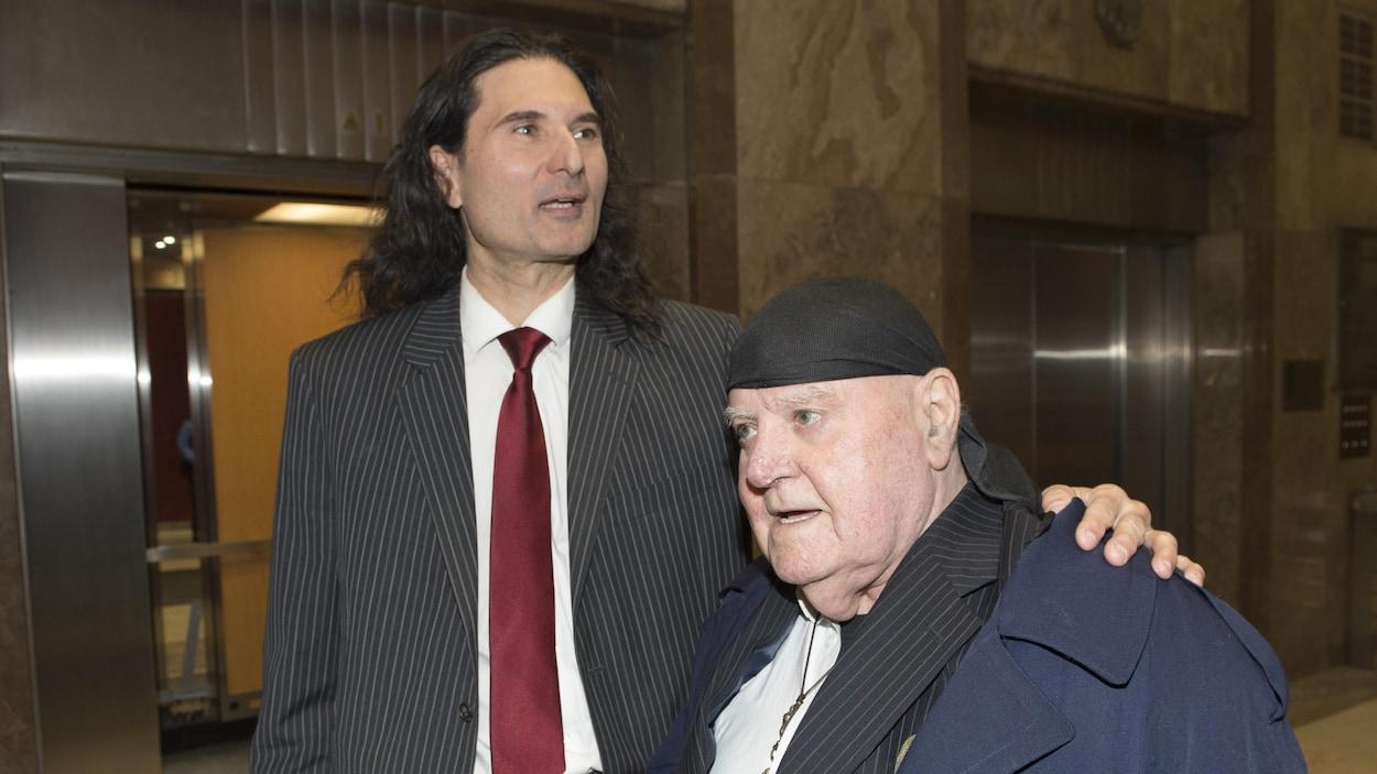Photo de deux hommes en complet près d'ascenseurs dans un édifice.