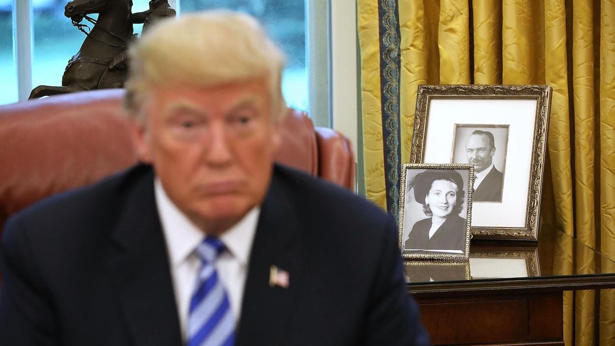 On voit le président Trump à l'avant-plan, mais le point focal porte sur des photographies en noir et blanc de ses parents, sur une table derrière lui.