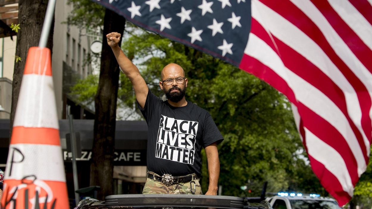 Le nom de George Floyd est écrit sur le pare-brise alors que John Coy porte un t-shirt sur lequel on peut lire « Black Lives Matter » et se tient debout à travers son toit ouvrant, le poing en l'air, 16e rue nord-ouest, rebaptisée « Black Lives Matter Plaza » près de la Maison-Blanche, le vendredi 19 juin, à Washington.