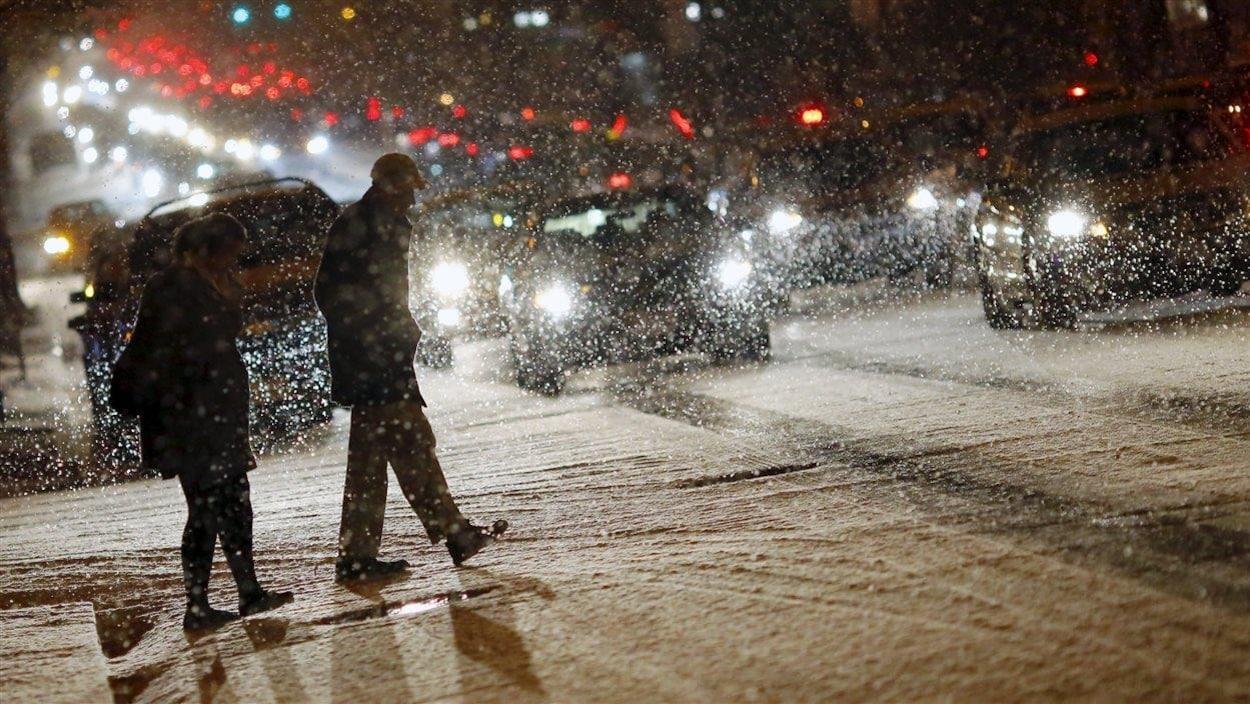 Des piétons déambulent dans les rues sous la neige.