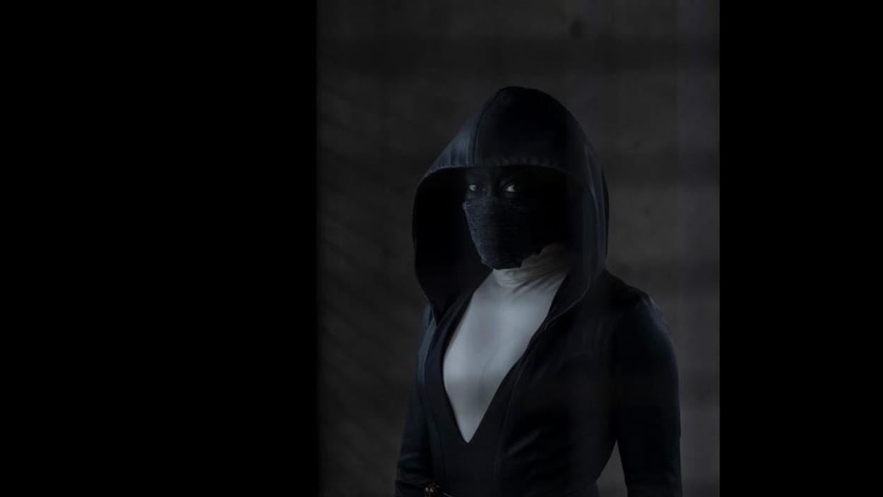Une femme masquée porte un manteau noir avec un grand capuchon sur la tête. Elle regarde droit dans l'objectif de la caméra.