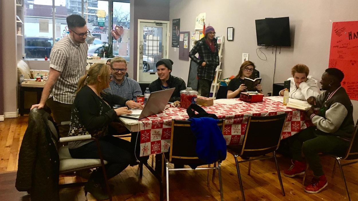 Sept personnes sont autour d'une table, l'air rieur, une autre marche vers la table, une est absorbée par sa lecture.