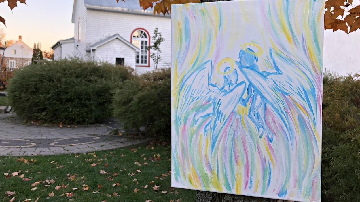 Une toile représentant deux anges est accrochée à un arbre.