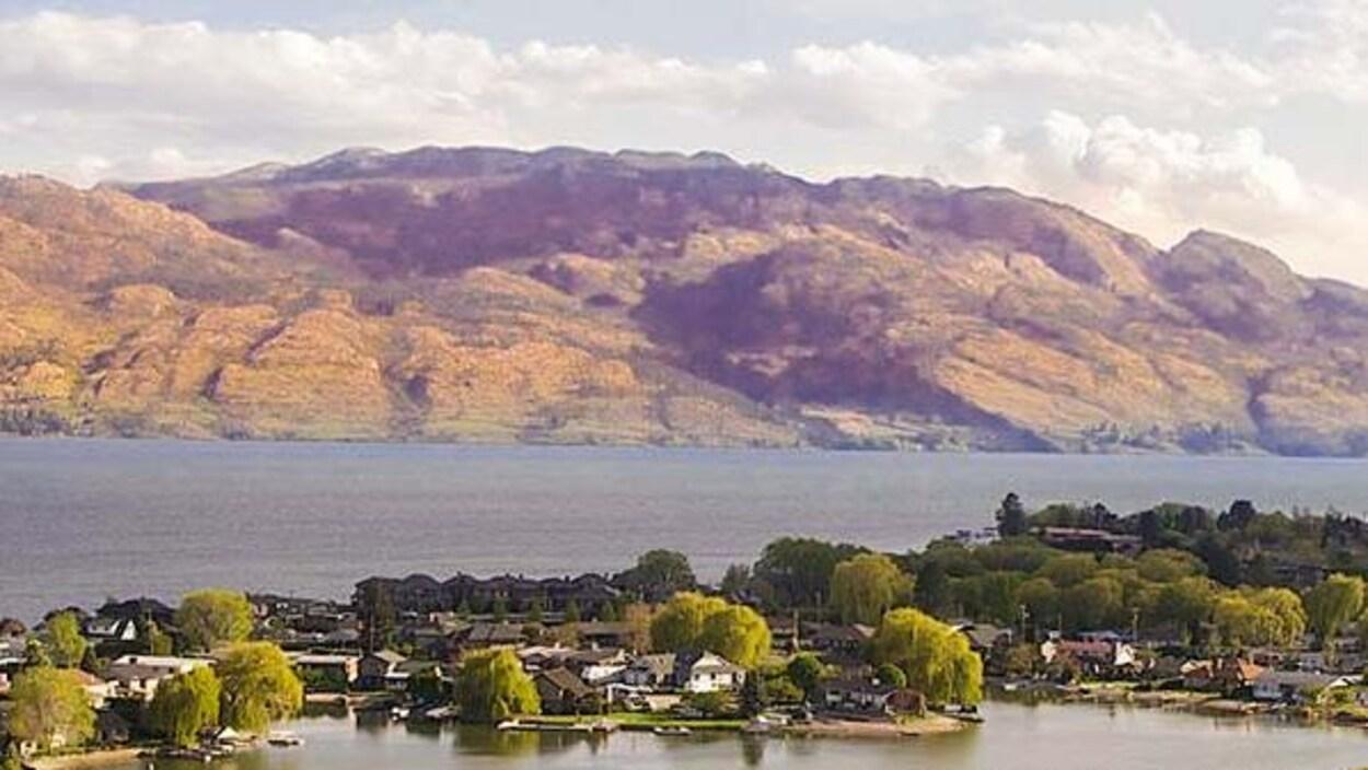 Vue aérienne de maisons devant un lac et des montagnes.