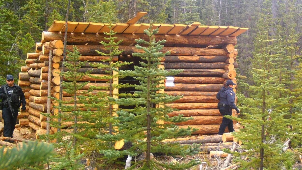 Deux agents patrouillent autour d'une petite loge en bois rond.