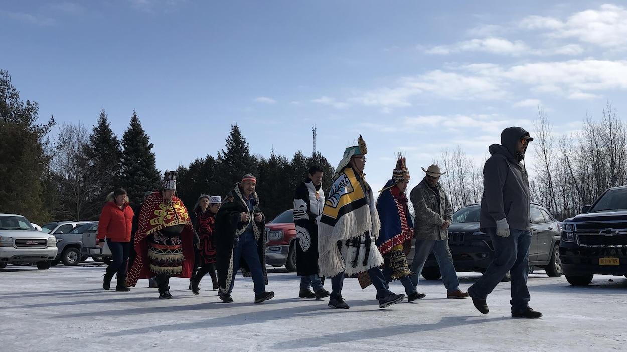 Des Autochtones en tenue traditionnelle marchant dans un stationnement
