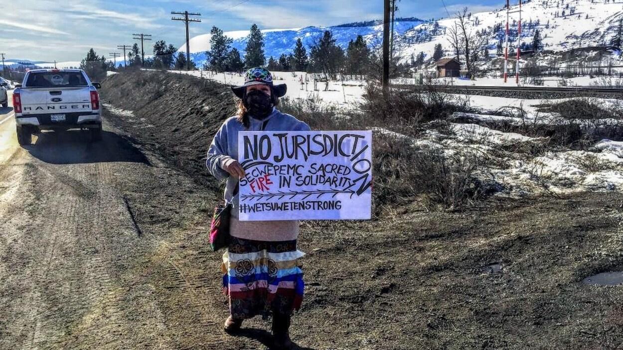 Une femme tient une affiche en solidarité avec les Wet'suet'en qui sont opposés au gazoduc Coastal GasLink près des voies ferrées du Canadien Pacifique entre Chase et Kamloops, en Colombie-Britannique.