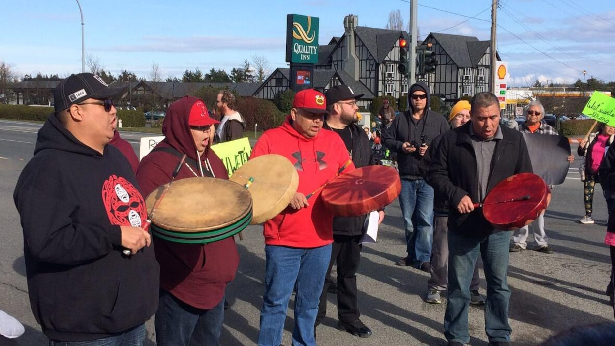 Des manifestants autochtones jouent du tambour sur une autoroute de l'île de Vancouver.
