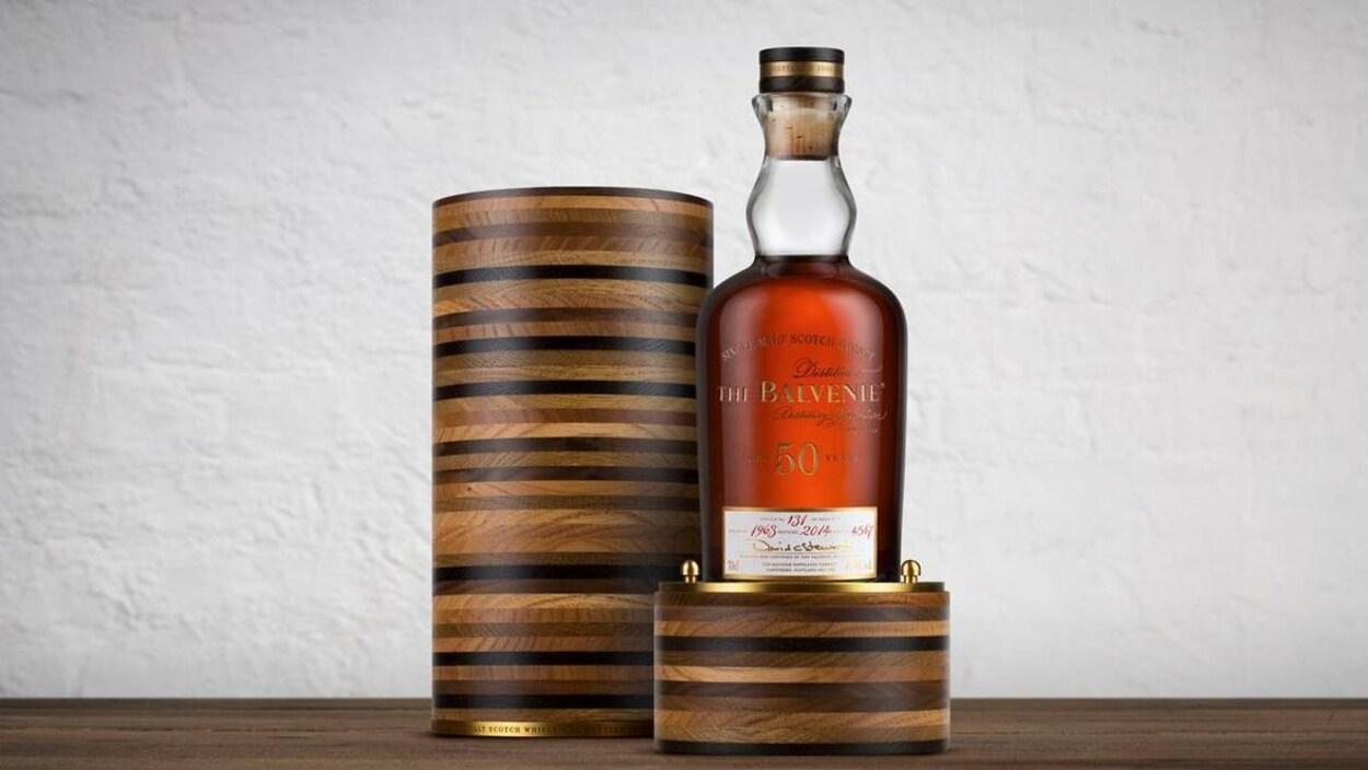 La bouteille est posée à côté de sa luxueuse boite. Le whisky est de couleur ambrée.