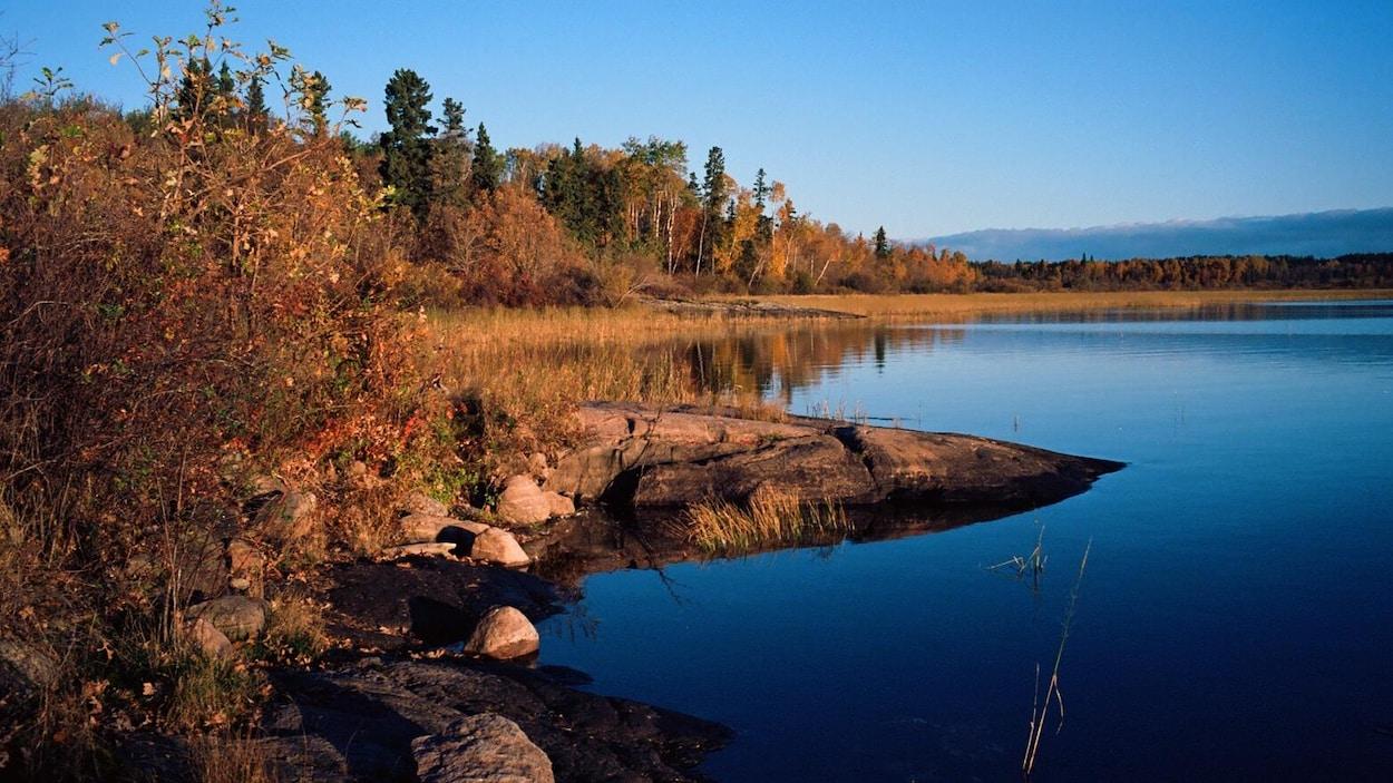 Le soleil se lève sur un lac très bleu.