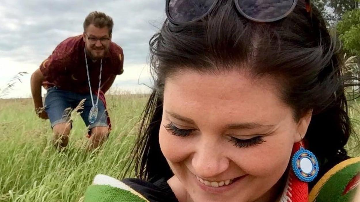 Une femme et un homme dans un champ de blé vert.