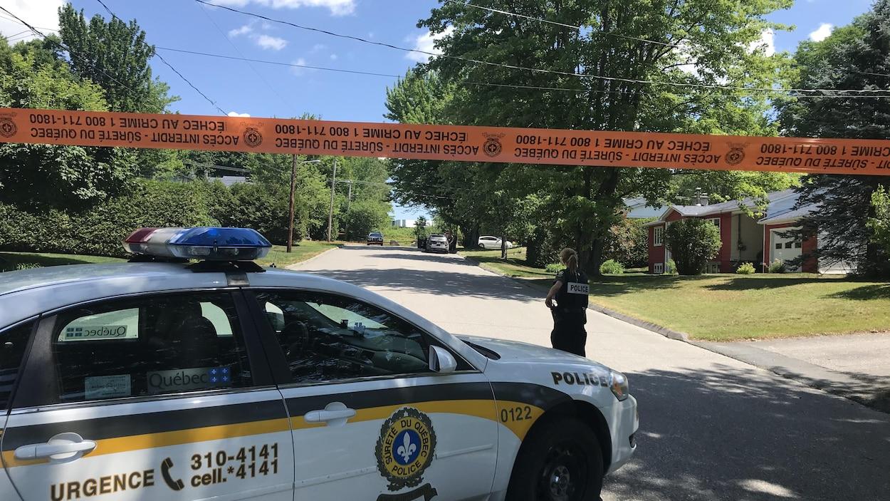 Une voiture de la Sûreté du Québec et une policière devant une rue bloquée par du ruban orange.