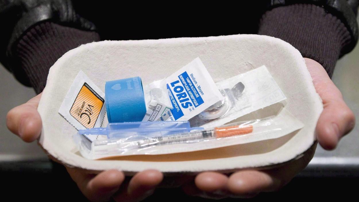 Deux mains tiennent un petit plat de carton avec tous les objects stérilisés nécessaires à l'injections de drogue comme une seringue.