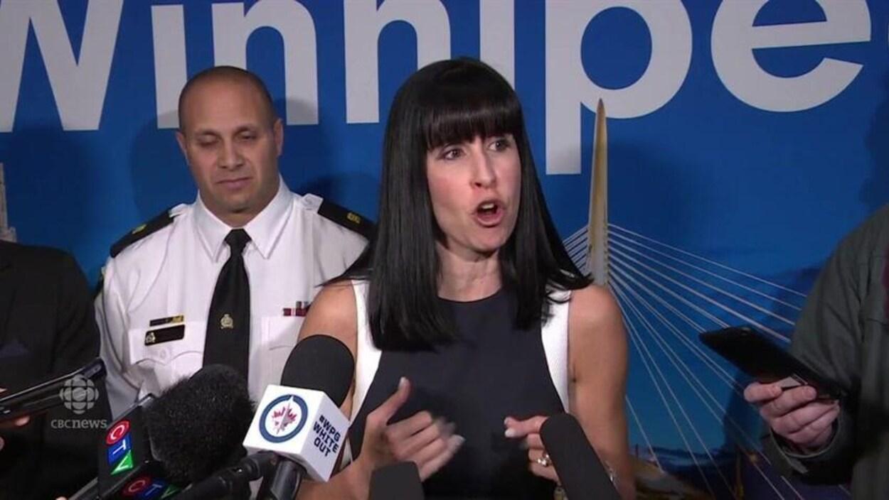 Une femme s'adresse aux journalistes.