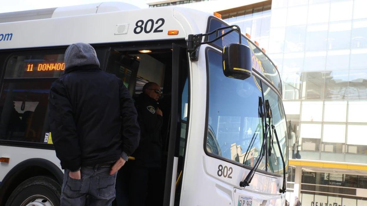 Un homme attend de monter dans un autobus municipal