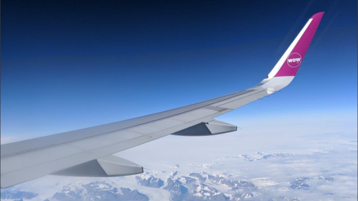 Vue d'un hublot d'une aile de l'avion avec le logo Wow Air et une vue aérienne de montagnes.