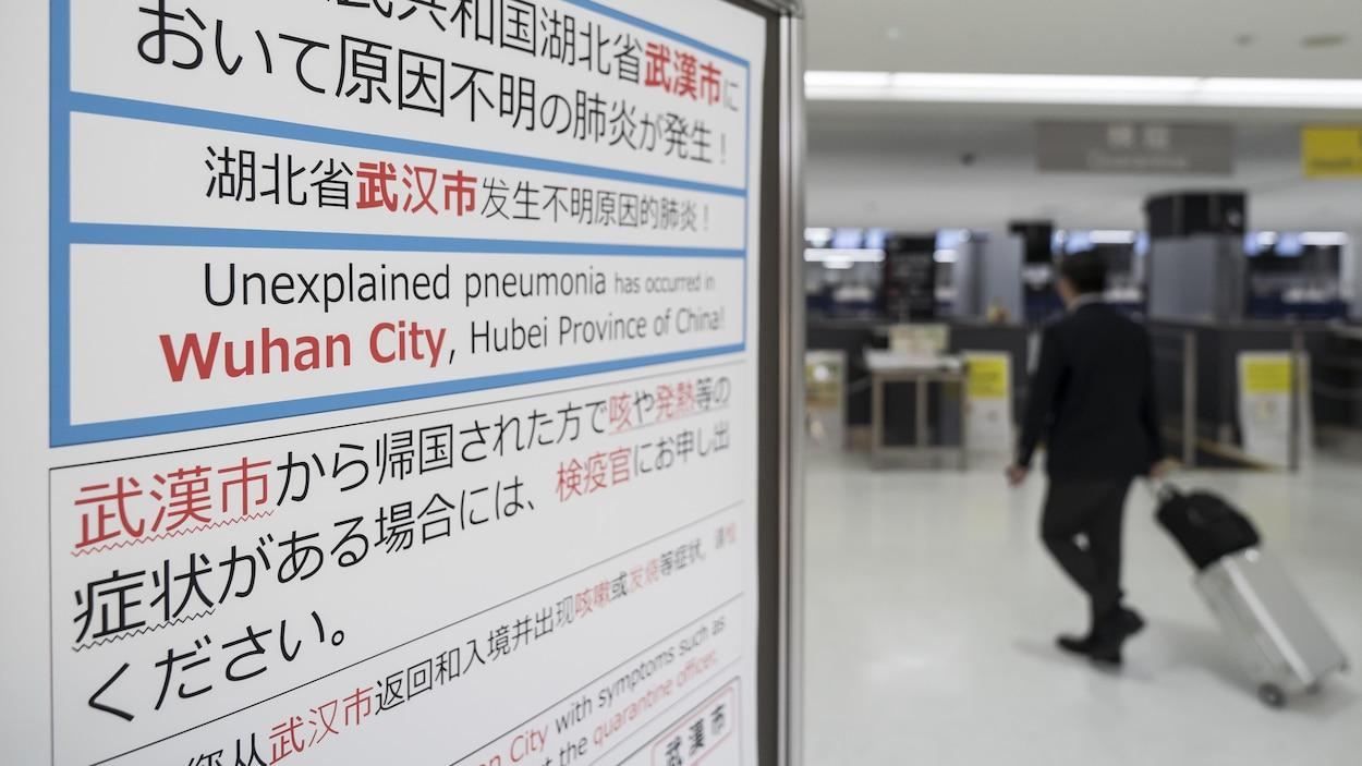 Un voyageur passe près d'une affiche écrite en anglais et en mandarin qui demande aux gens de déclarer leurs symptômes s'ils sont grippés.