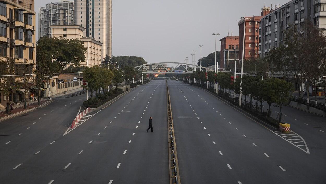 Un homme marche seul au milieu d'un boulevard urbain.