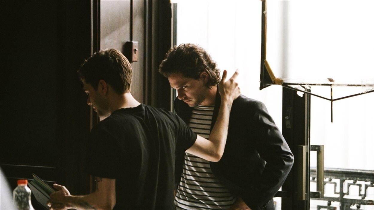 Xavier Dolan tient Kit Harington par l'épaule tout en lisant quelque chose sur le plateau de «The Death and Life of John F. Donovan».