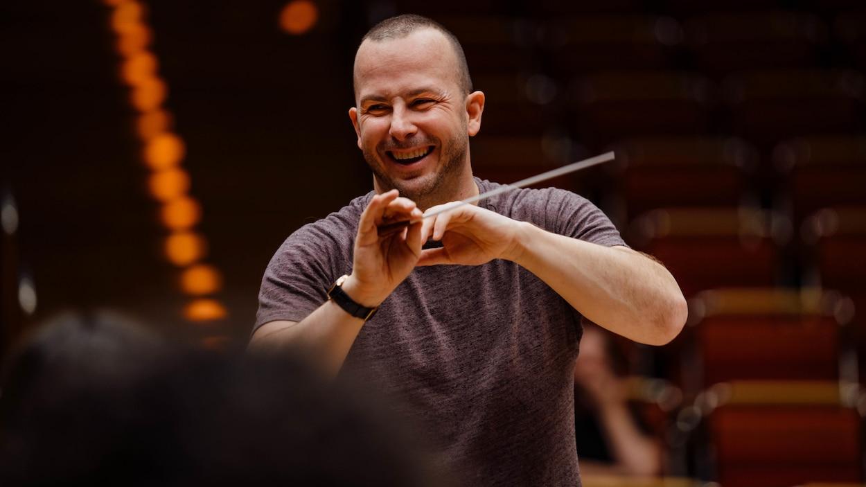 L'homme sourit alors qu'il tient une baguette de chef d'orchestre dans sa main.