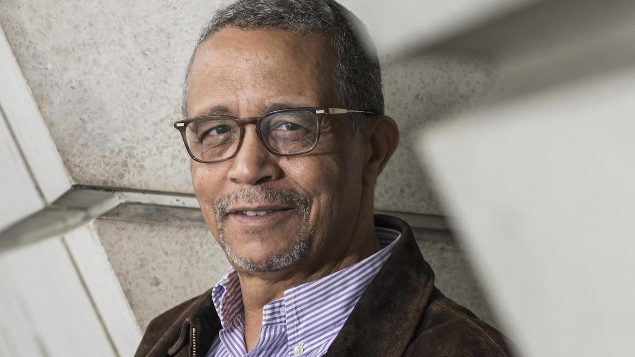 Un homme, cheveux grisonnant très courts et portant des lunettes, est appuyé sur un mur de béton. Il porte une chemise rayé bleu et blanc sous une veste de cuir brun et regarde la caméra.