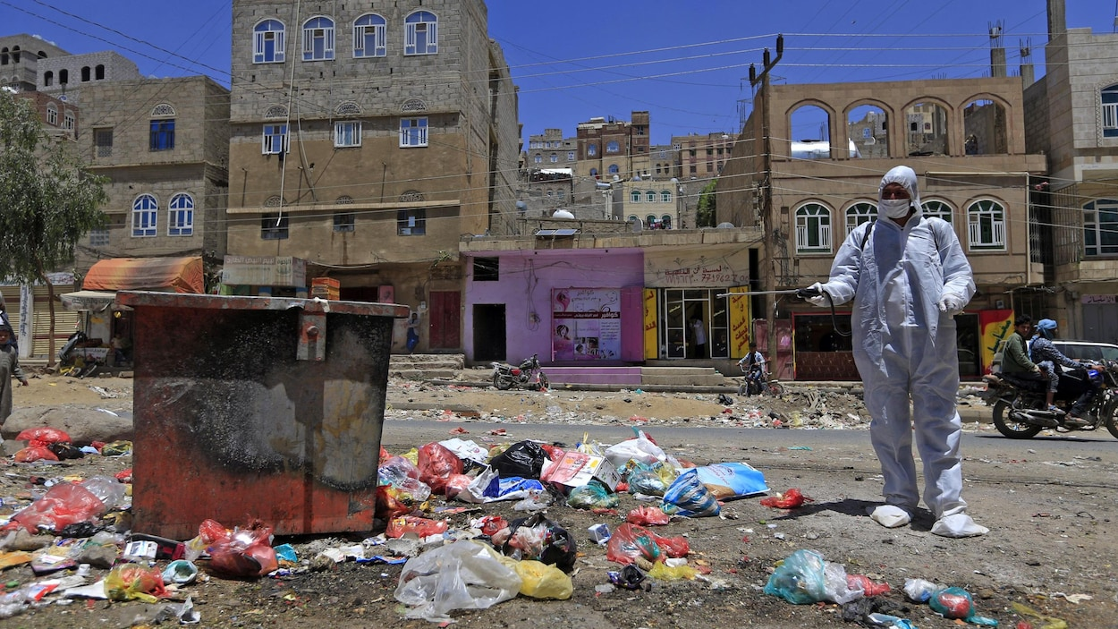 Un homme en tenue de protection désinfecte des ordures dans une ville au Yémen pour prévenir la propagation du nouveau coronavirus.