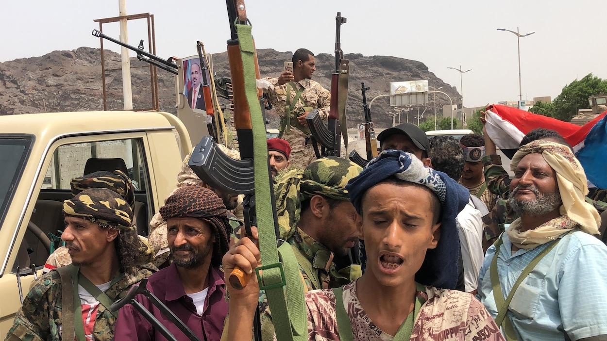 Des hommes armés posent près d'une jeep.