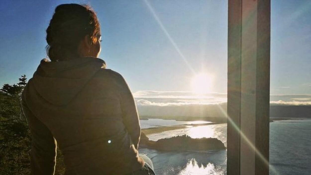 Une jeune femme de dos, assise sur le rebord d'une galerie extérieure, regarde la mer et le soleil.