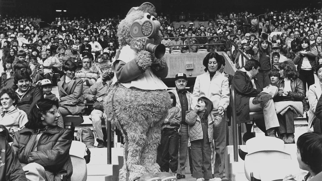 Mascotte Youppi entourée de la foule dans le stade tient une caméra de Radio-Canada.