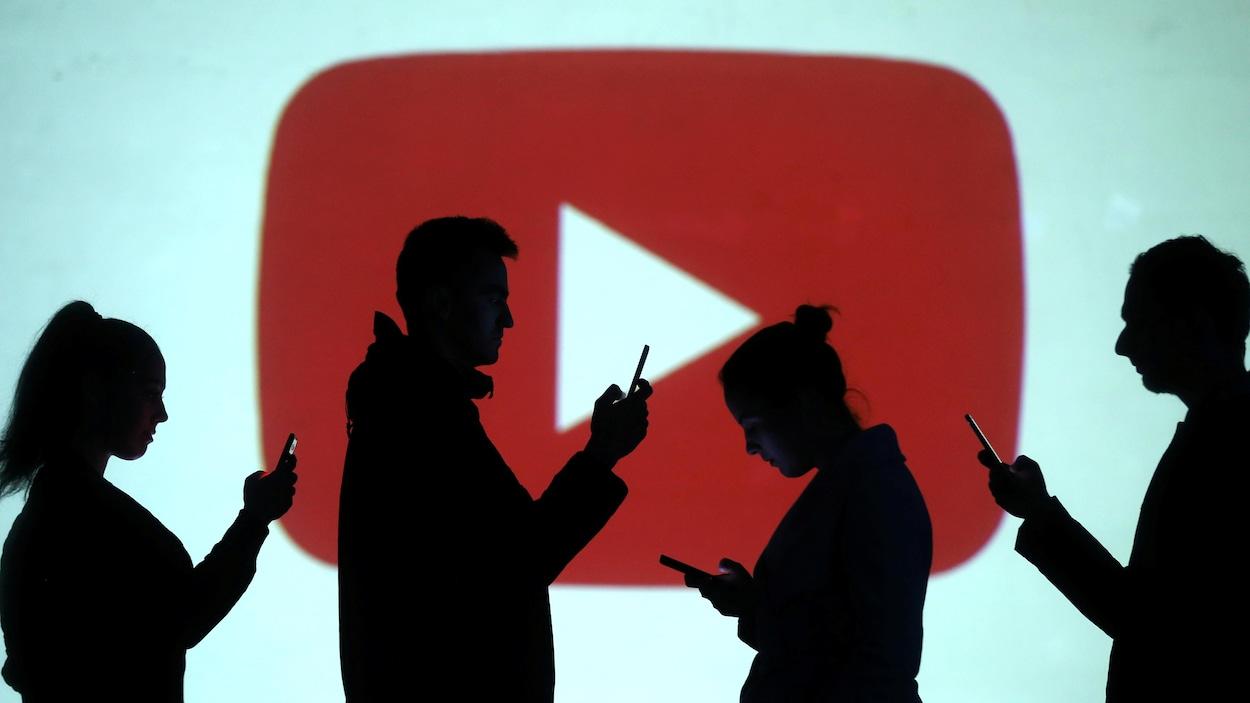 Des silhouettes regardent des téléphones devant un arrière-plan du logo de YouTube.