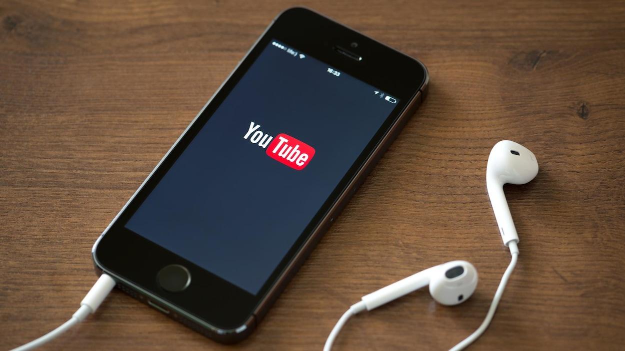 Le logo de YouTube est affiché sur un téléphone intelligent posé sur une surface en bois.