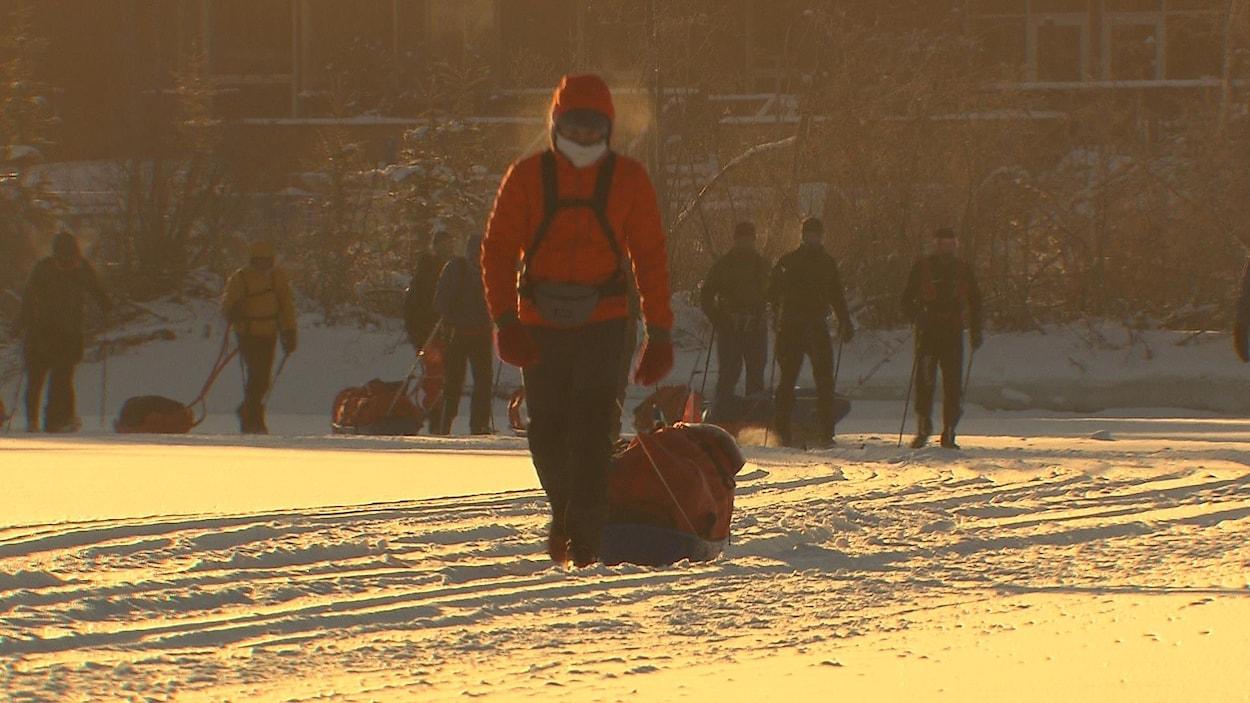 Huit personnes marchent dans la neige en s'aidant de bâtons et en transportant de l'équipement dans leurs sacs à dos.