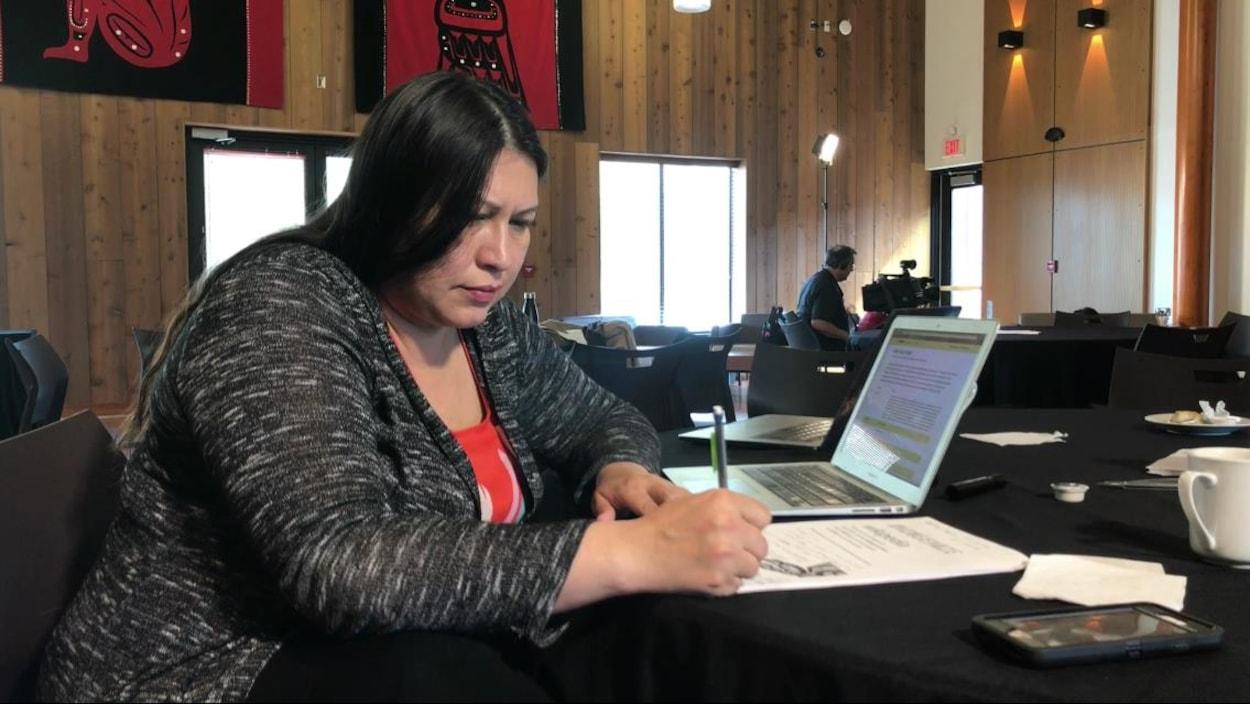 Une femme assise à un bureau prend des notes au stylo sur un document posé à côté d'un ordinateur portatif.