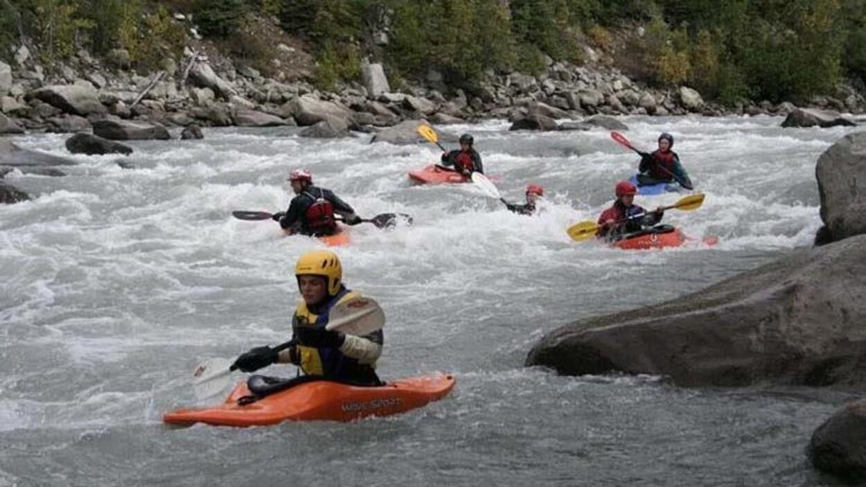 Des jeunes en kayak pagaient dans des rapides sur un cours d'eau.