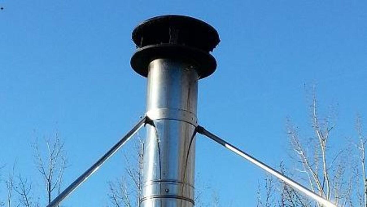 Une cheminée noircie sur un toit de tourbe.