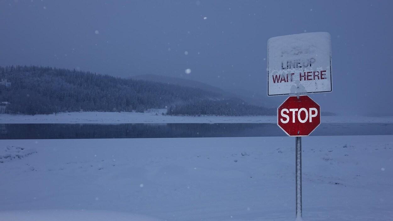 enseigne d'arrêt à l'endroit où un pont de glace l'hiver et un traversier l'été relient les deux rives