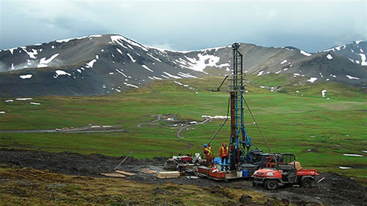 Équipement de forage avec deux travailleurs au milieu des montagnes.