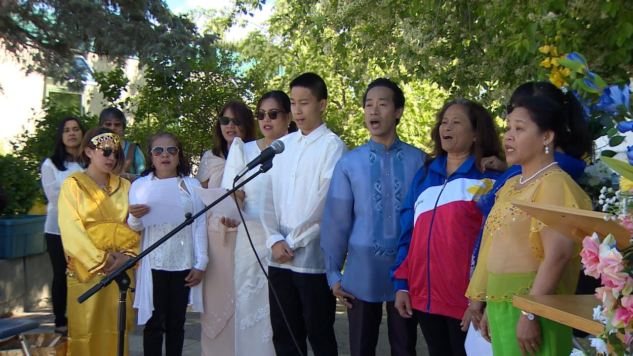 Des membres de la communauté philippine chantent l'hymne national.