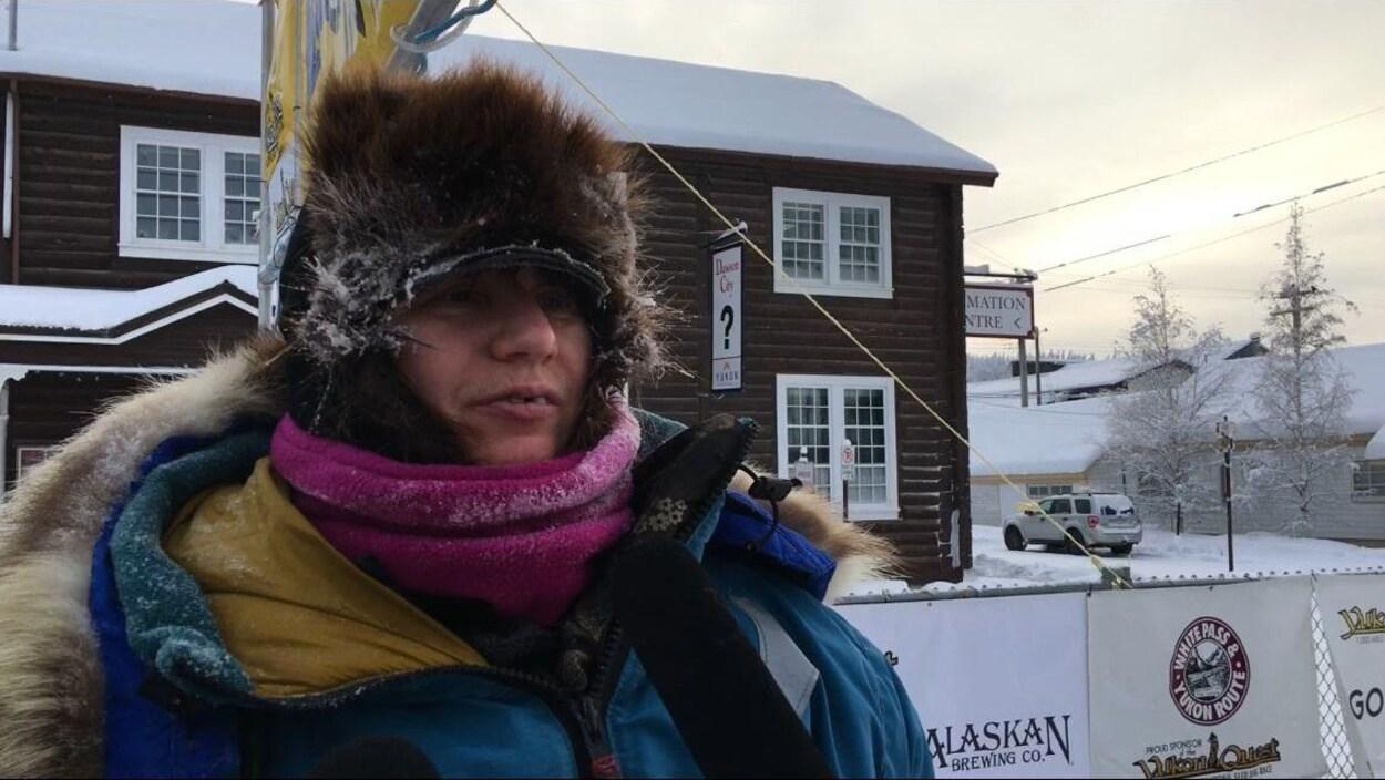 Une femme habillée chaudement devant un édifice en rondins.