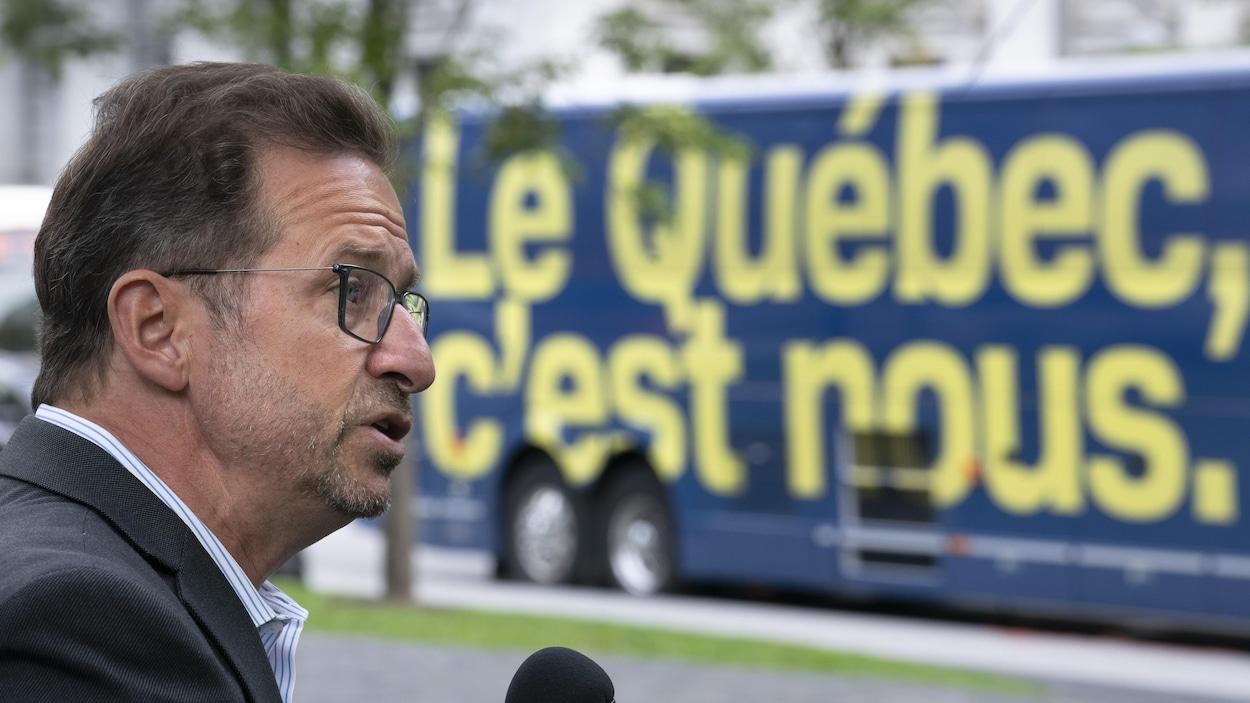 Yves-François Blanchet est de profil et parle au micro. Derrière lui, l'autobus du Bloc québécois est stationné.