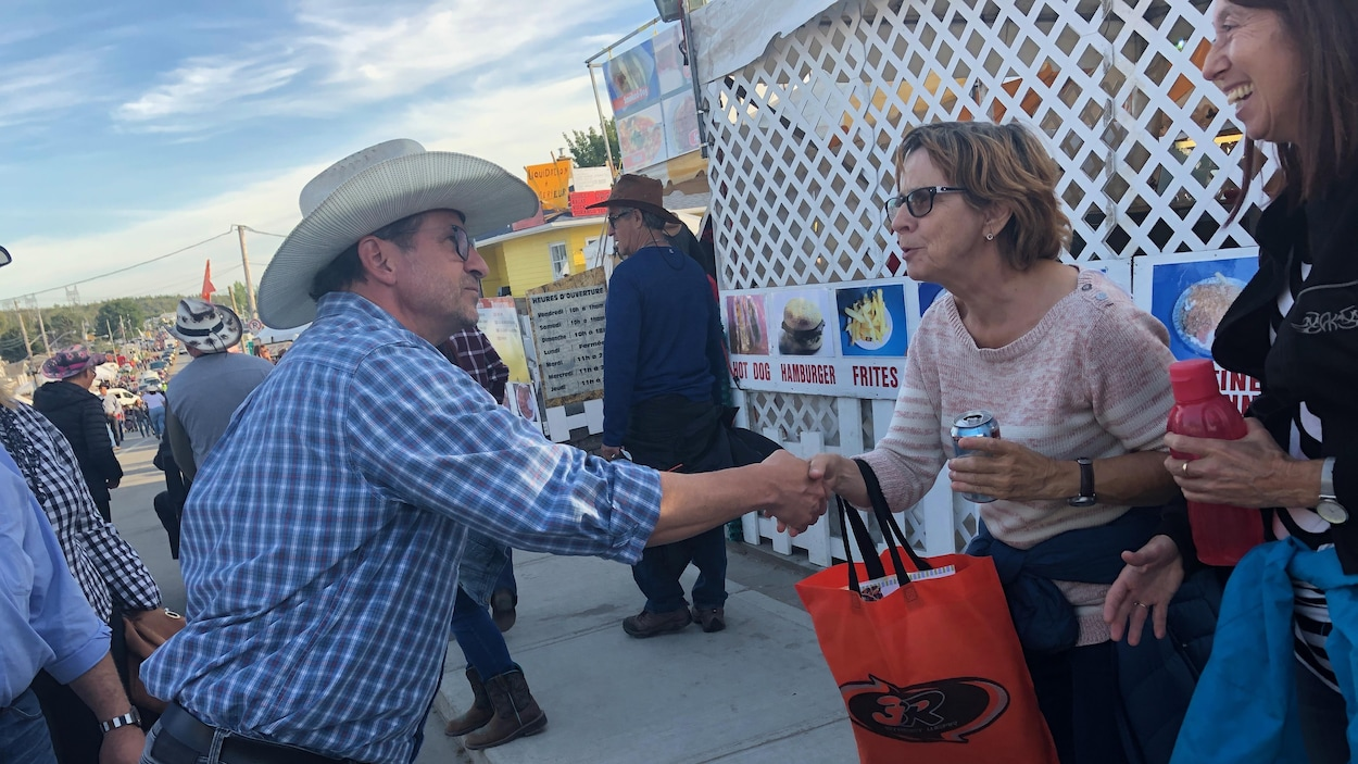 Yves-François Blanchet porte un chapeau de cowboy et serre la main d'une femme.