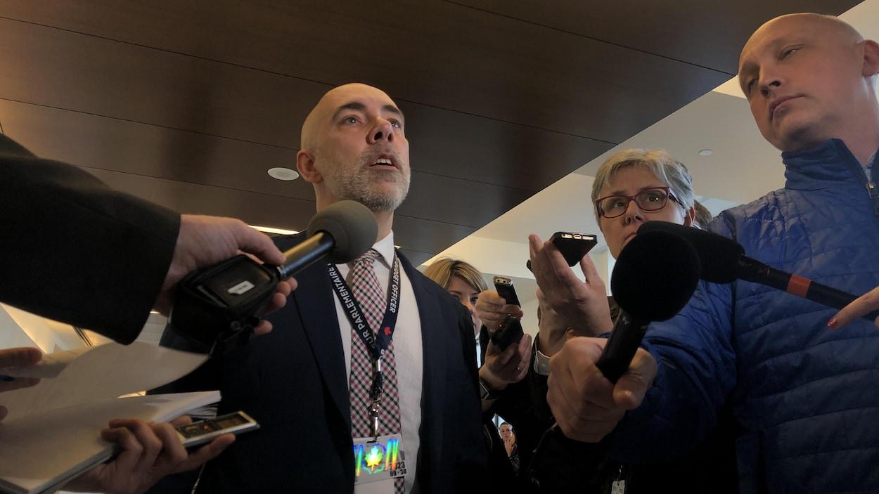 M. Giroux est entouré de journalistes qui lui tendent un micro.