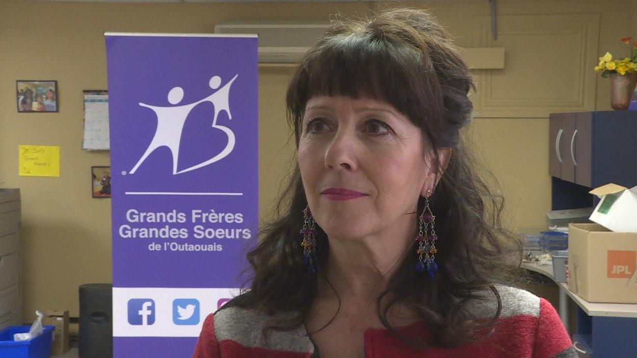 Une dame aux cheveux bruns devant une bannière de l'organisme.