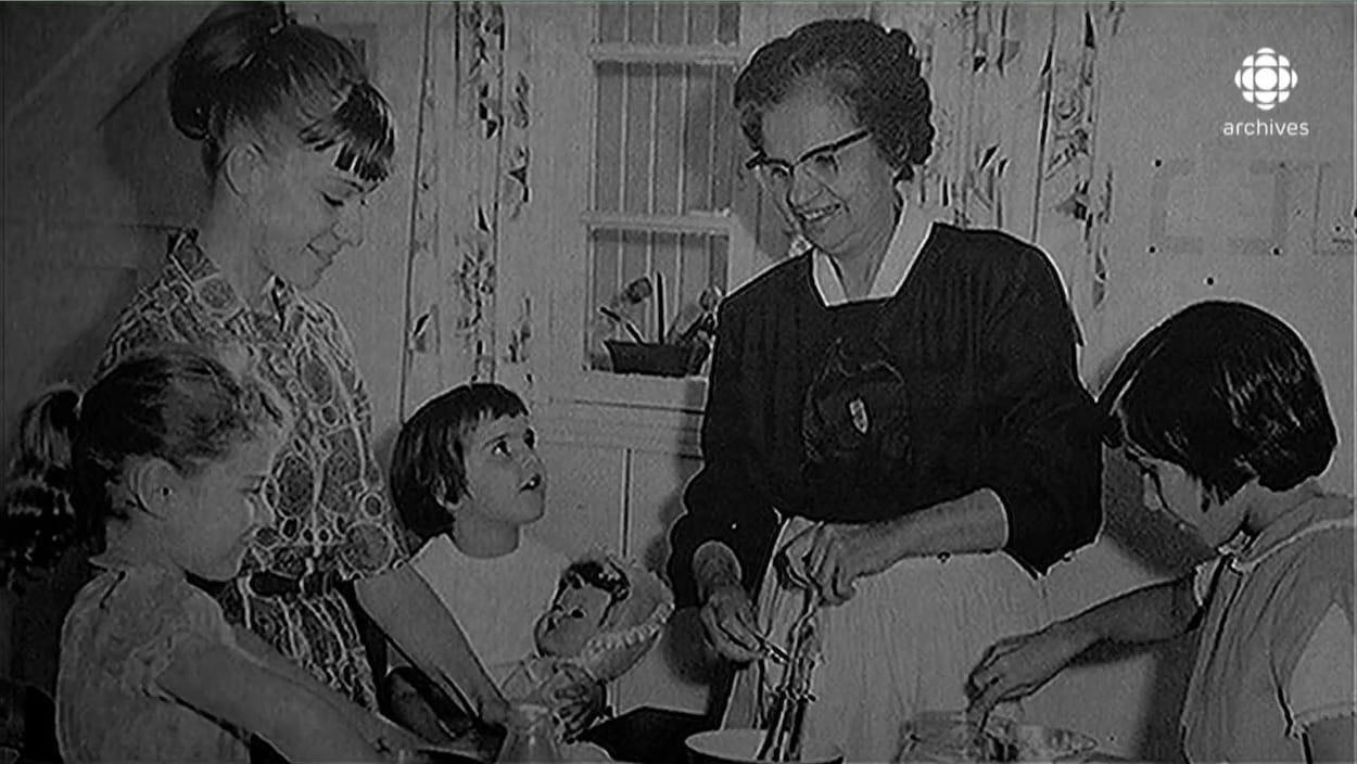 Photo en noir et blanc d'Yvonne Maisonneuve, cuisinant aux côtés d'une jeune fille et de trois enfants